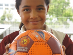 Female student holding soccer ball